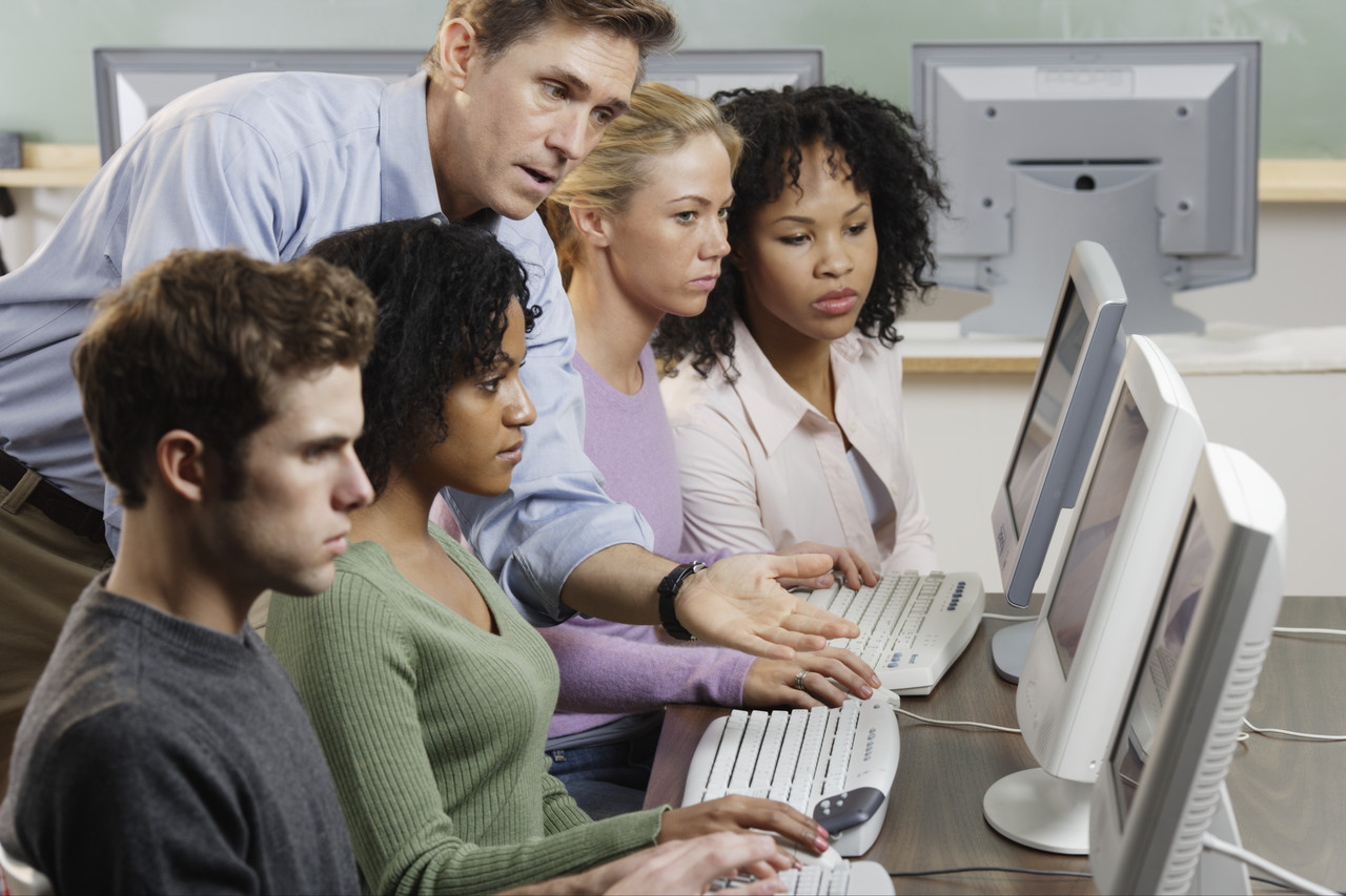 Instructor with students in computer lab image by royalty free